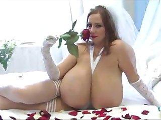 The bosomy girl masturbates sniffing red rose