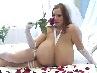The bosomy girl masturbates sniffing red rose